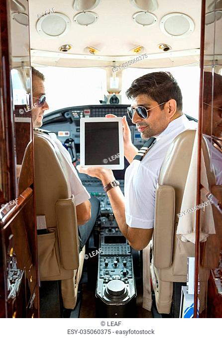Pilot showing digital tablet to copilot in cockpit of private jet