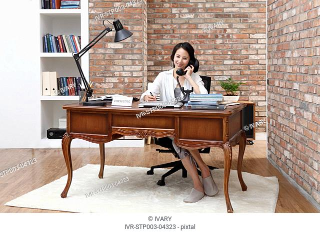 A young woman in an office talking on the phone