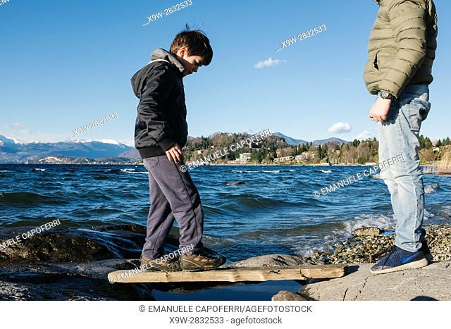 Children play among the rocks on the beach of Lake Maggiore