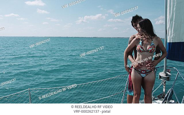 Couple kissing while standing on deck of sailing