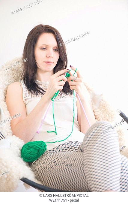 Woman knitting. She is sitting in a chair in home interior. Lifestyle image showing leisure activity and hobby