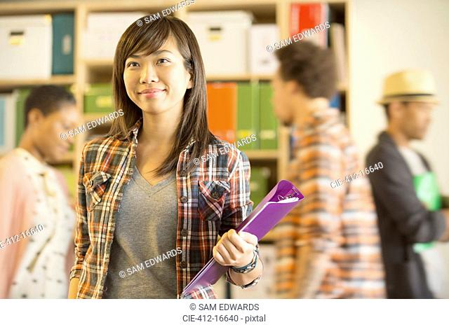 Portrait of confident casual businesswoman with co-workers passing in background