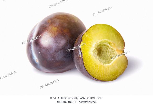 Whole and half of violet plums near isolated on white background
