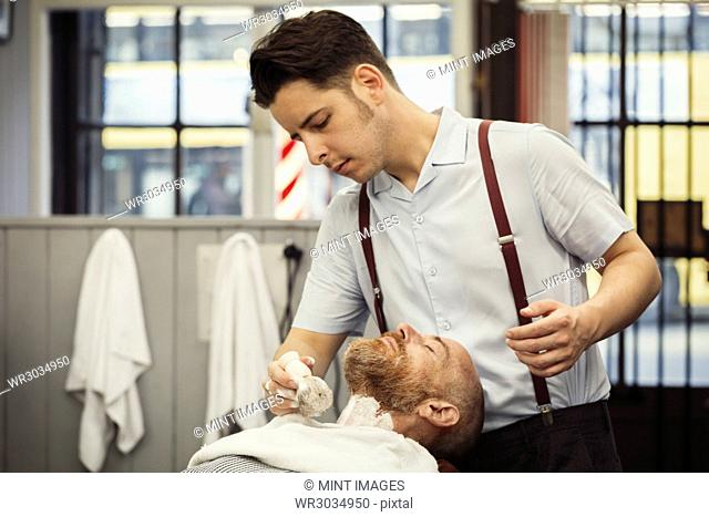 A customer sitting in the barber's chair, having a wet shave. A man using a shaving brush to lather his chin and neck