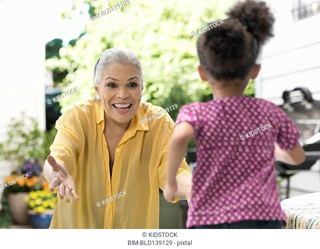 Older grandmother greeting granddaughter