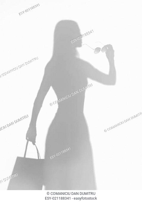 woman elegantly holding a pair of sunglasses, silhouette