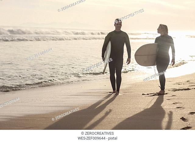 Couple with surfboards walking on the beach at sunset