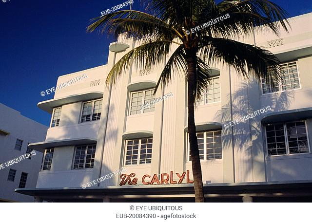 South Beach. Ocean Drive. The Carlyle Hotel seen in early morning light with a palm tree casting a shadow on the exterior