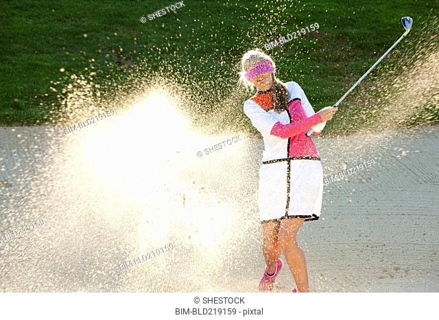 Caucasian woman hitting golf ball in sand trap while blindfolded