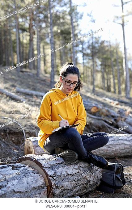 Young woman with yellow sweater in the forest, writing