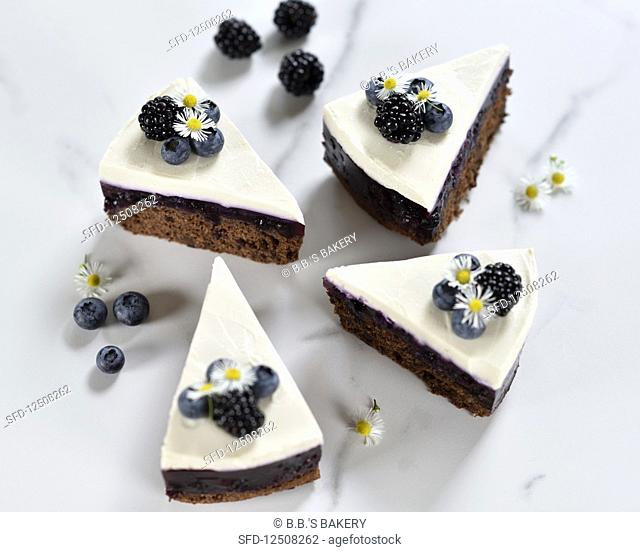 Vegan chocolate and blueberry cake with a cream cheese topping and fresh berries