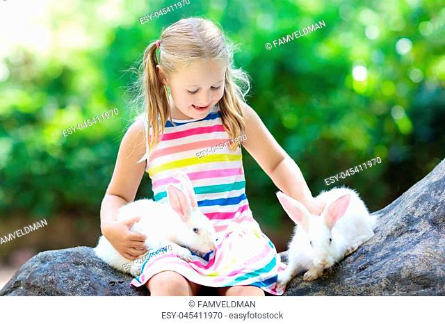 Child playing with rabbit. Little girl feeding white bunny. Easter celebration. Egg hunt with kid and pet animal. Children and animals
