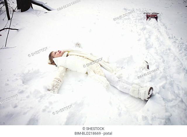 Caucasian girl making snow angel in field