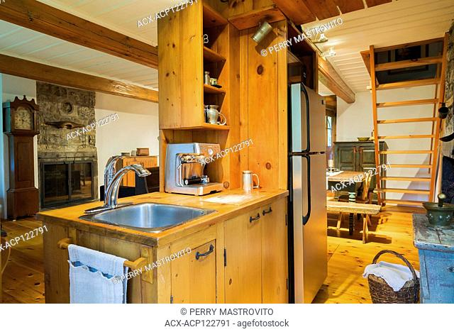 Small rustic kitchen with pinewood countertop and sink cabinet, floorboards inside an old circa 1750 Canadiana style fieldstone house, Montreal, Quebec, Canada