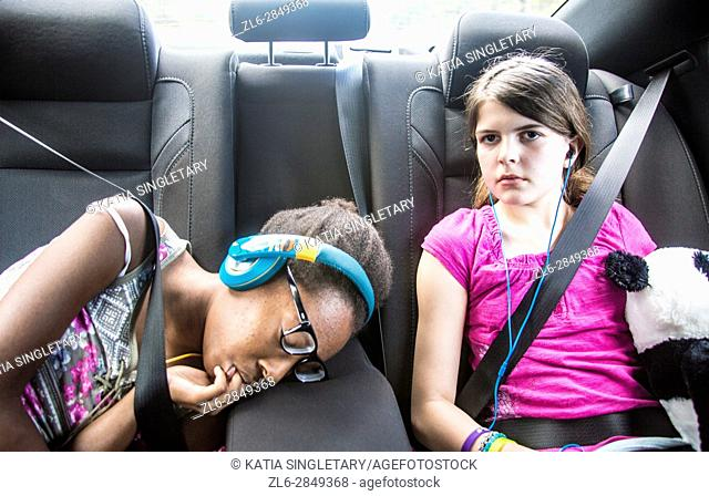 2 girls, one caucasian preteen and one african american teen sucking her fingers in the car sleeping and resting with stuff animals and earphones on
