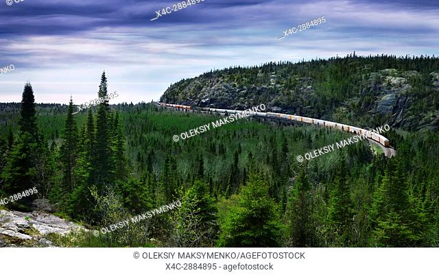 Canadian Pacific Railway, CP Rail freight train passing around a rocky hill by the shore of Lake Superior. Ontario, Canada, aerial landscape scenery