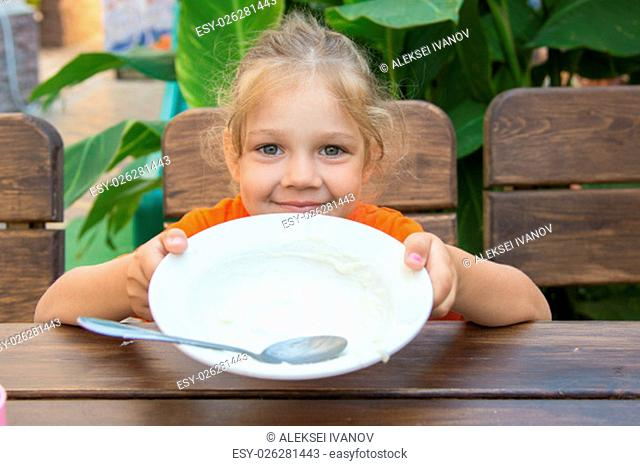 Five-year girl ate all the porridge in a plate and shows an empty cup