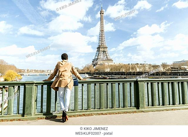 France, Paris, Female tourist looking towards the Eiffel tower and the Seine river