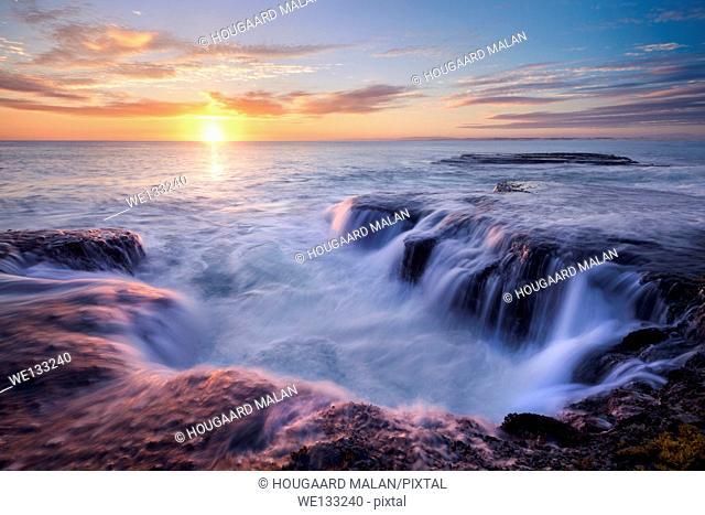 Landscape phot of a sunrise sky over seaside rocks. Arniston/Waenhuiskrans, Western Cape, South Africa