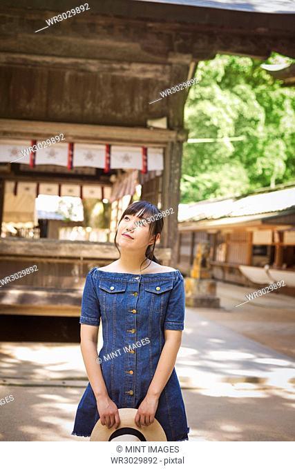 Young woman wearing blue dress and holding hat at Shinto Sakurai Shrine, Fukuoka, Japan