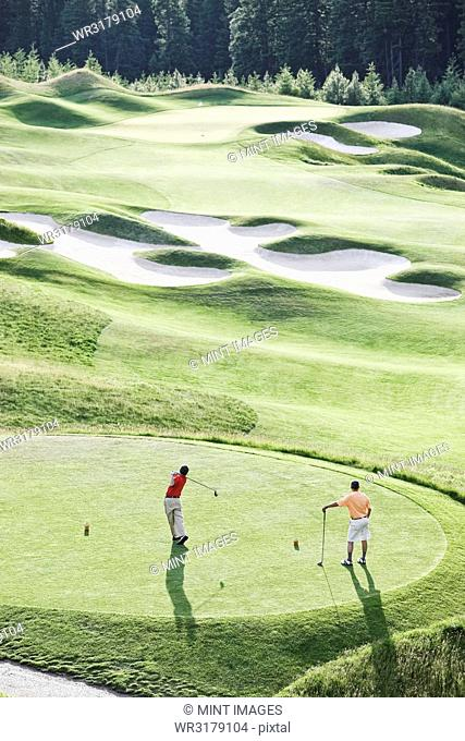 View from above of two golfer teeing off on a golf course