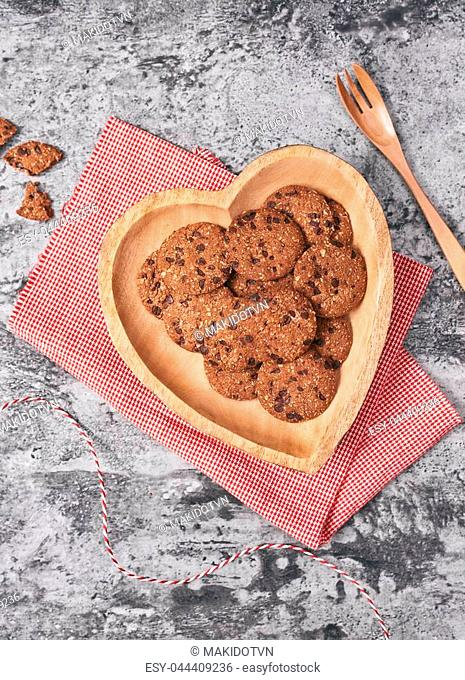 Cookies on wooden heart-shaped plate. Gift for Valentine's Day