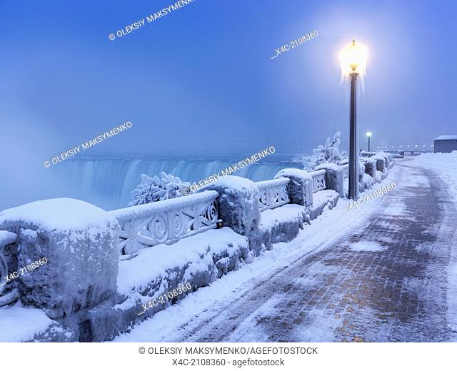 Sidewalk covered with snow and a lamp post, tranquil city scenery at Niagara Falls. Horseshoe waterfall wintertime scenic. Ontario, Canada