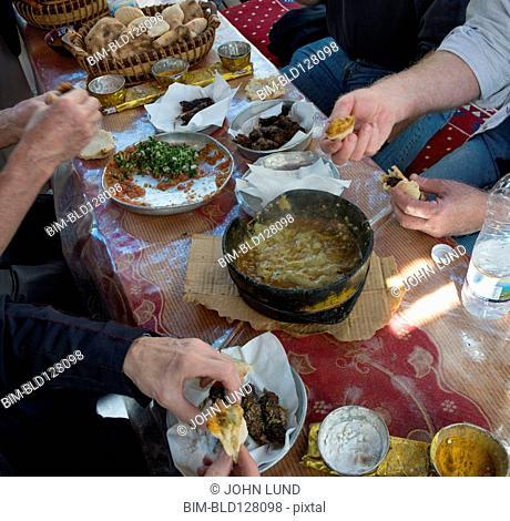 People eating Yemeni food at table, Saana, Yemen