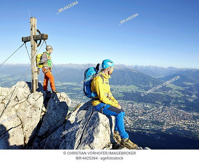 Summit cross Nordkette, two climbers enjoying view at top, Nordkette Innsbruck, Tyrol, Austria