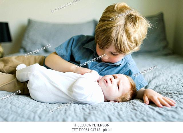 Boy and his baby brother on bed