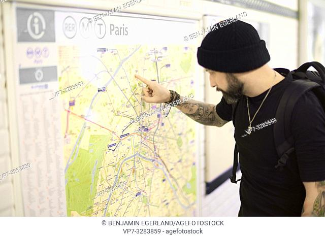 Man looking at map in subway station. Paris, France