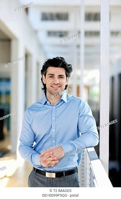 Businessman leaning on railing, portrait