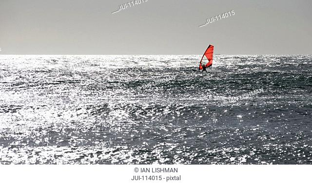 Windsurfer windsurfing on sunny windy ocean