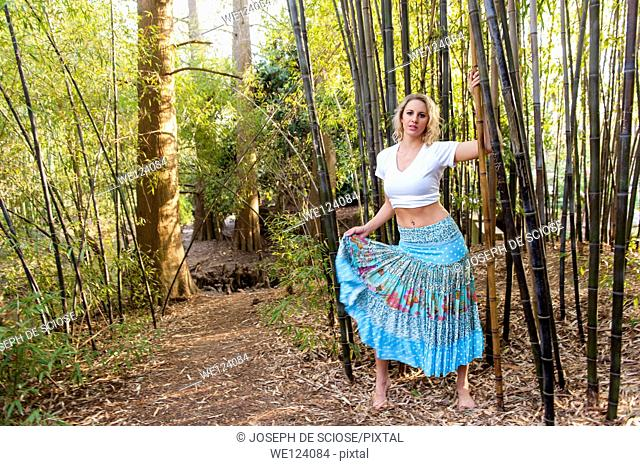 A happy 22 year old blond woman wearing a skirt and white top walking among bamboo canes in a garden
