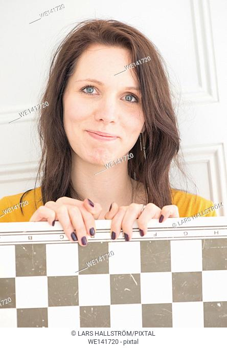 Smiling woman holding chessboard in home interior. Concept of strategy, leisure activity and playing games
