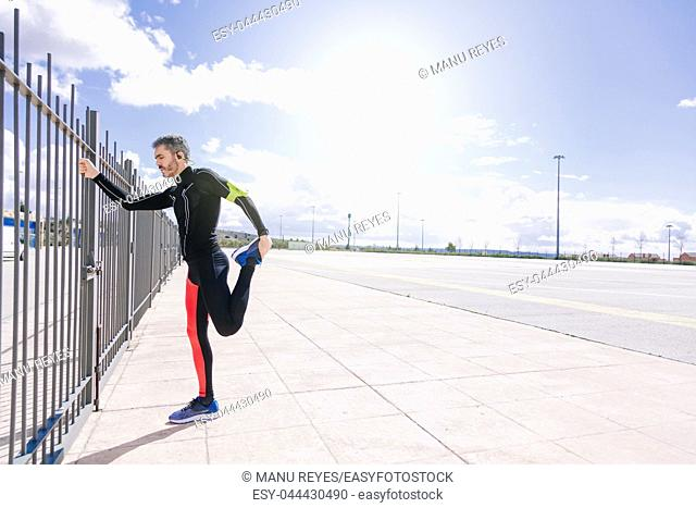 young adult man stretching on the outdoors before to run