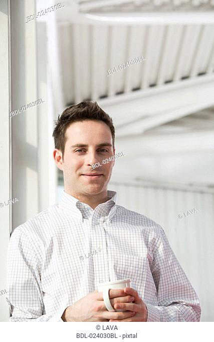 portrait of young businessman holding cup