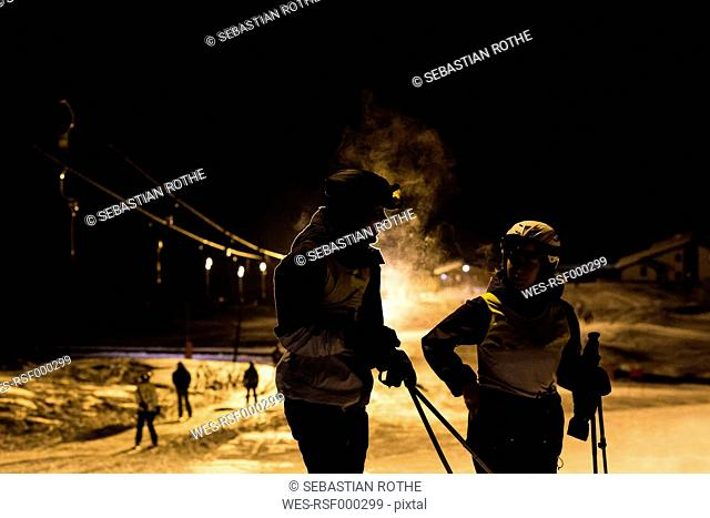 Austria, Sellrain, Gries, two skiers in floodlight at night