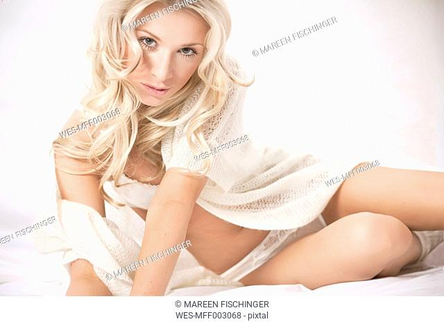 Blond woman in lingerie sitting on bed