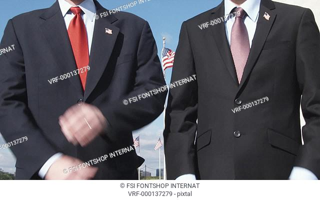 CU, Lockdown of two well-dressed men crossing their arms in front of American flags, Washington DC