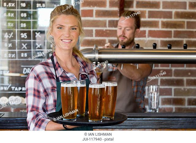 Portrait Of Waitress By Counter In Bar With Tray Of Drinks