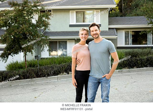 Portrait of smiling couple in front of their home