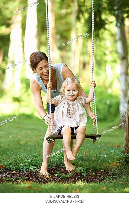 Mid adult mother pushing toddler daughter on garden swing