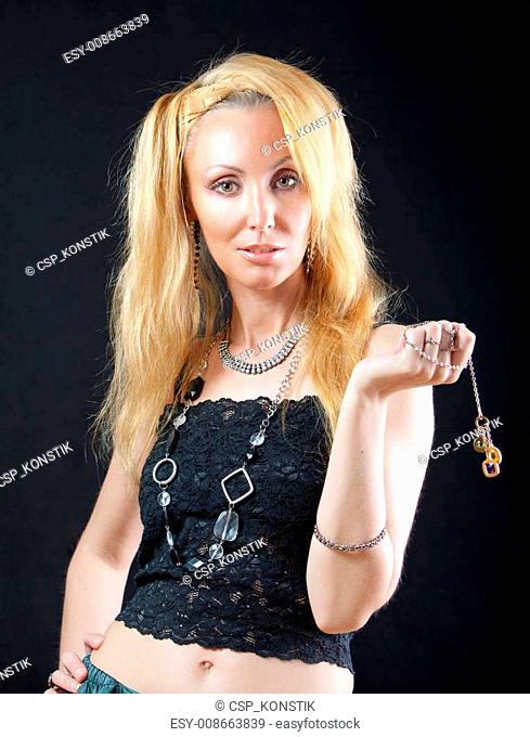beautiful young blonde woman with long hair and jewellery on dark background