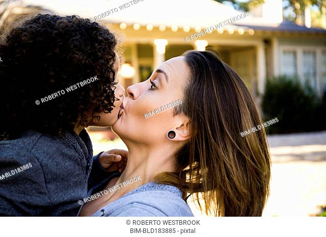 Mother kissing son outdoors