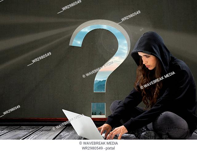 Woman hacker using a laptop in a room with question mark on it
