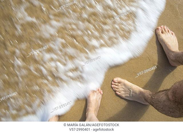 Man and woman's feet at the sea shore