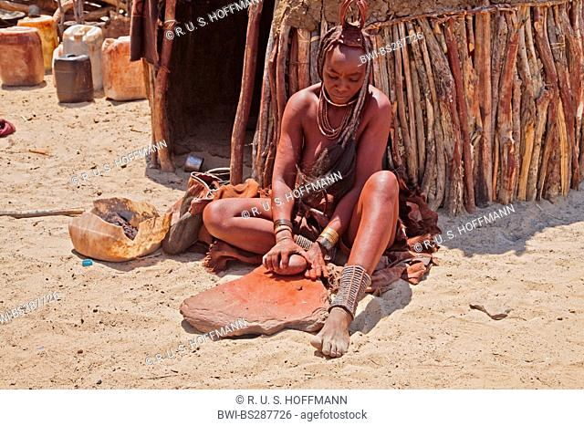 himba woman sitting in front of her hut and grinding up ocher, Namibia