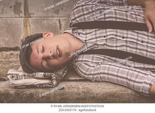 Old style retro portrait of a news paperboy out cold on a paper pillow. Don't kill the messenger