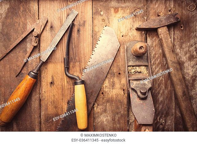 Od vintage hand tools on wooden background. Carpenter workplace. Tinted photo